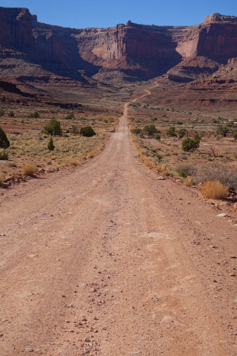 Dirt road heading to a beautiful rock outcropping in an open landscape. Analogy of your financial practices journey.