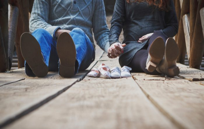 Couple holding hands with baby shoes. Analogy is running your household as a small business is worth the effort.
